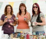 Three women holding tins and jars at a charity stall